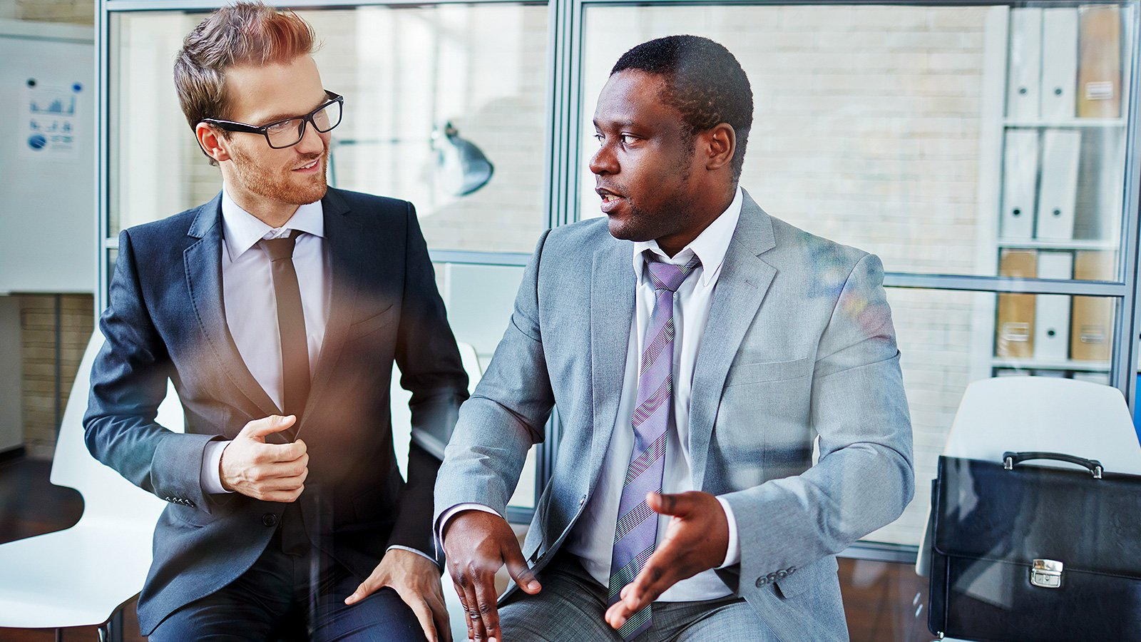 Two businessmen sitting side-by-side engaged in a discussion.