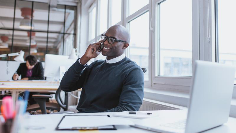 young-man-talking-on-his-mobile-phone-in-office_800x450